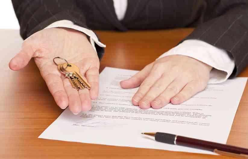 Frau hält Schlüssel und Mietvertrag in Händen
